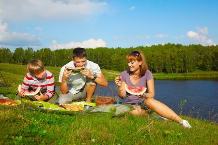 outdoor portrait of happy families eating watermelon at the picnic near camp tent photo