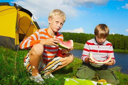 outdoor portrait of two boys eating watermelon on green grass near camp photo
