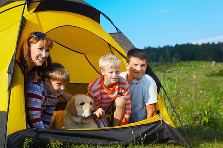 holiday pets: family outdoor portrait of smiling mother, two boys, young man and labrador looking happy outside of tent