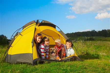 summer girl: family outdoor portrait of smiling mother, two boys, young man and labrador looking happy outside of tent