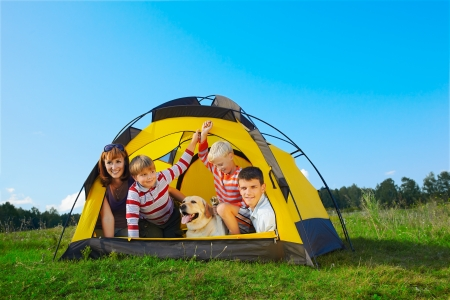 family outdoor portrait of smiling mother, two boys, young man and labrador looking happy outside of tent