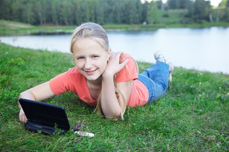 outdoor portrait of happy smart young girl laying on green grass with small laptop photo