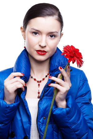 isolated portrait of beautiful brunette girl in blue jacket with red gerbera flower photo