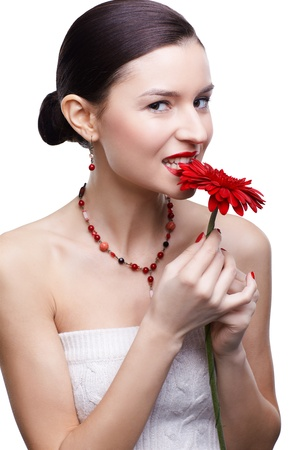 isolated portrait of beautiful tempting brunette girl biting red gerbera flowers petal photo
