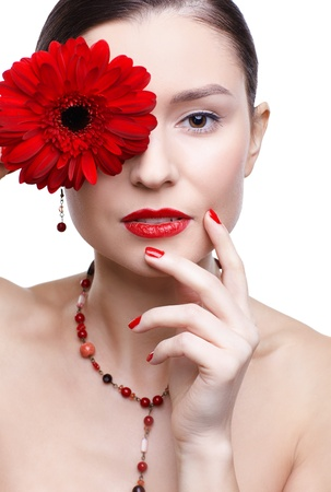 isolated portrait of beautiful brunette girl hiding her eye behind red gerbera flower photo
