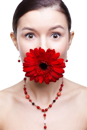 isolated portrait of beautiful brunette surprised girl with red gerbera flower in her mouth photo