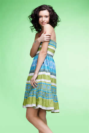 portrait of beautiful curly brunette girl in summer dress posing on green photo