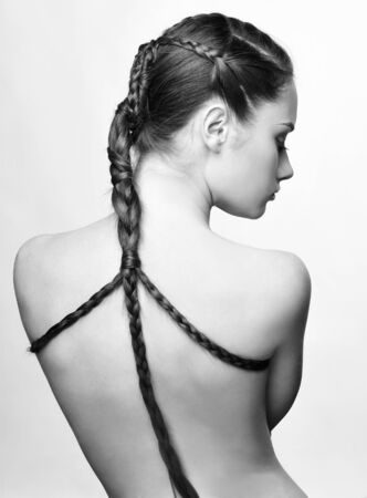 hairstyle portrait of beautiful brunette girl with creative braid hairdo standing back to camera Stock Photo - 8936241