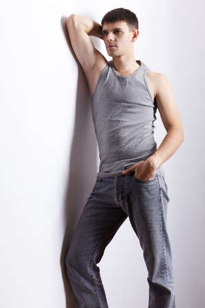 undershirt: portrait of young handsome brunet guy in undershirt and jeans posing on gray Stock Photo