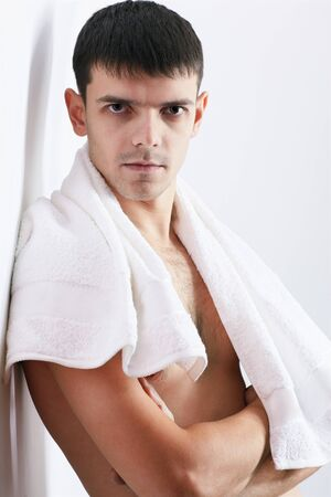 portrait of healthy handsome brunet guy posing with towel on his neck photo