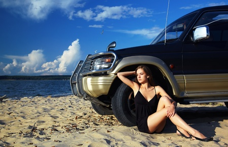 Young beautiful slavonic girl sitting on the sand in black dress near the off-roaders wheel  photo