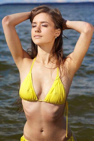 Young beautiful slavonic girl in yellow bikini posing on the beach Stock Photo - 9074831