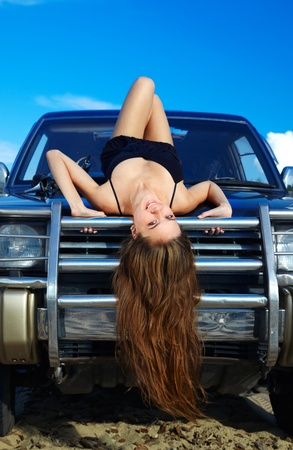 Young beautiful slavonic girl in black dress posing on the cowl of off-road car. photo