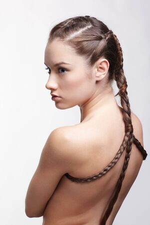 hairstyle portrait of beautiful brunette girl with creative braid hairdo standing back to camera Stock Photo - 9154461