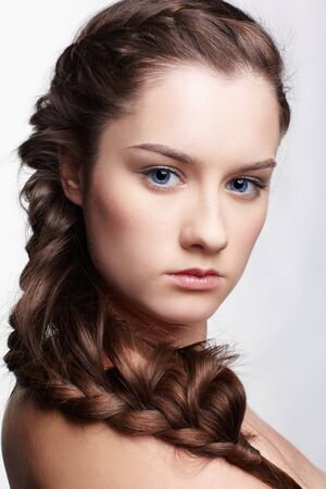 hairstyle portrait of beautiful brunette girl with creative braid hairdo photo