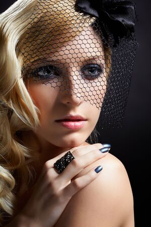 glamour portrait of beautiful blonde retro girl in veil on dark photo