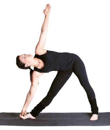 utthita: full-length portrait of beautiful woman working out yoga excercise utthita trikonasana  on fitness mat