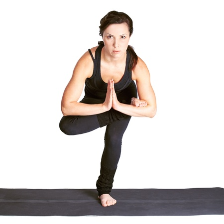 full-length portrait of beautiful woman working out yoga excercise. balancing on one leg on fitness mat photo