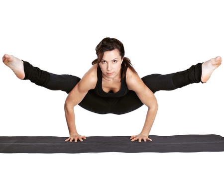 full-length portrait of beautiful woman working out yoga excercise tittibhasana - standing on hands ad doing the spilts on fitness mat photo