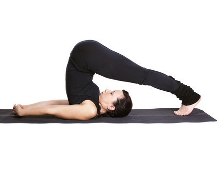 the plough: full-length portrait of beautiful woman working out yoga excercise halasana (plough pose) on fitness mat