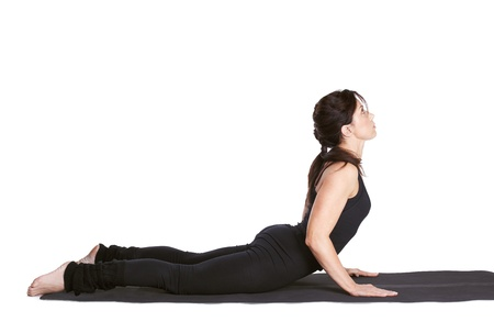 girl pose: full-length portrait of beautiful woman working out yoga excercise bhujangasana (cobra pose) on fitness mat Stock Photo