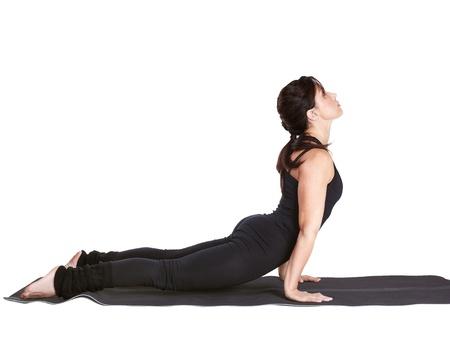 bhujangasana: full-length portrait of beautiful woman working out yoga excercise urdhva mukha shvanasana (cobra pose) on fitness mat