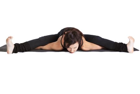 full-length portrait of beautiful woman doing the splits on fitness mat photo