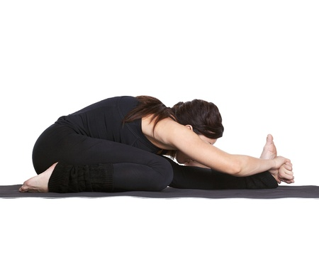 knee bend: full-length portrait of beautiful woman working out yoga excercise janu sirsasana (head to knee forward bend) on fitness mat