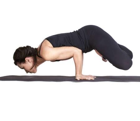 padma: full-length portrait of beautiful woman working out yoga excercise balancing on hands in padma mayurasana pose