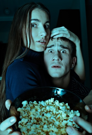 Young couple watching scary movie on tv photo