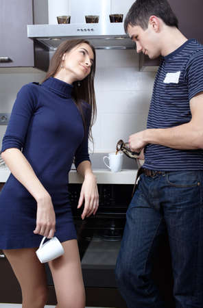 Young couple drinking coffee at the kitchen photo