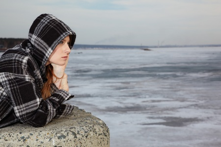 persona triste: Chica rubia cerca de R�o de invierno cubierto por hielo