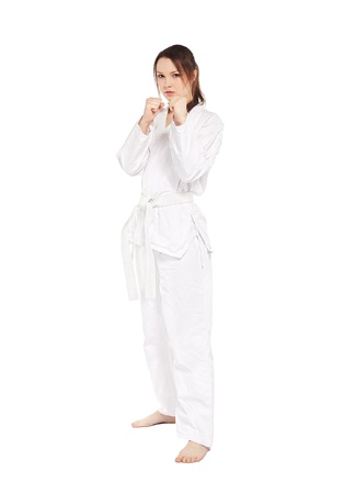 full-length isolated portrait of beautiful martial arts girl in kimono excercising karate kata photo