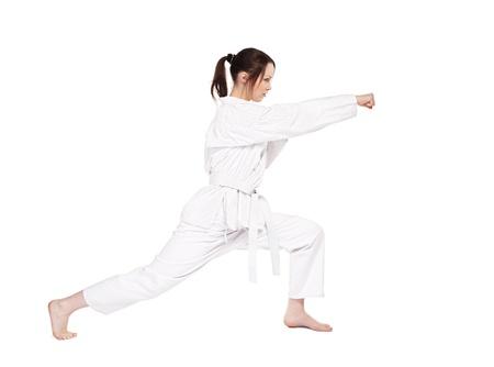 full-length isolated portrait of beautiful martial arts girl in kimono excercising karate kata photo