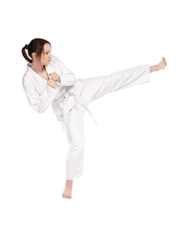 full-length isolated portrait of beautiful martial arts girl in kimono excercising karate kata kick photo