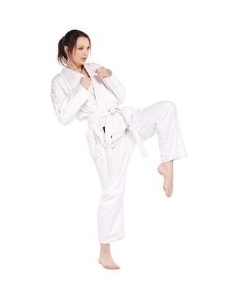 full-length isolated portrait of beautiful martial arts girl in kimono excercising karate kata kick Stock Photo - 9340233