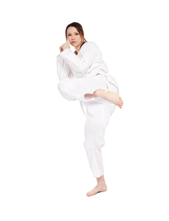 full-length isolated portrait of beautiful martial arts girl in kimono excercising karate kata kick Stock Photo - 9340199