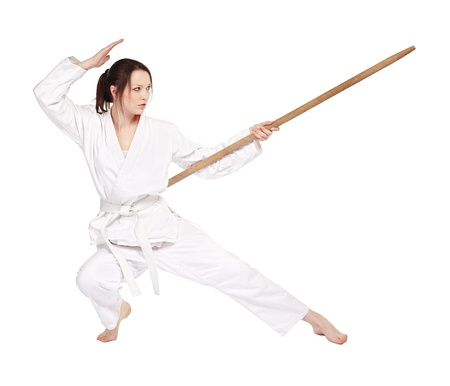 kata: full-length isolated portrait of beautiful martial arts girl in kimono excercising karate kata wit staff