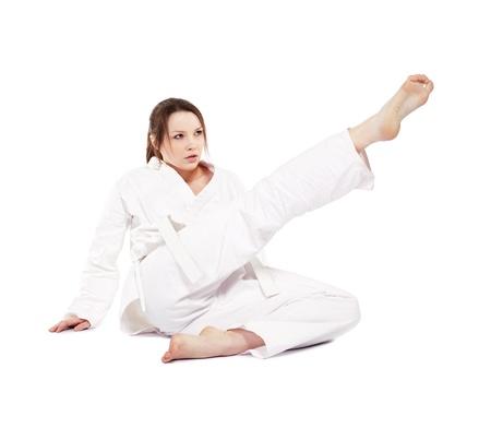 kata: full-length isolated portrait of beautiful martial arts girl in kimono excercising karate kata kick from the land