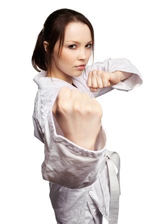 karate female: isolated portrait of beautiful martial arts girl in kimono excercising karate kata