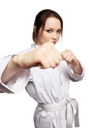 kata: isolated portrait of beautiful martial arts girl in kimono excercising karate kata