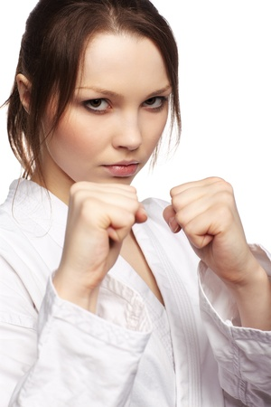 isolated portrait of beautiful martial arts girl in kimono excercising karate kata photo