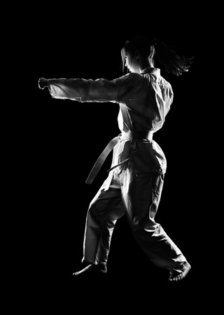 on strike: full-length silhouette portrait of beautiful martial arts girl in kimono excercising karate kata on black