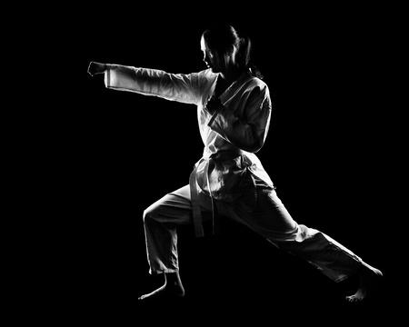 taekwondo: full-length silhouette portrait of beautiful martial arts girl in kimono excercising karate kata on black