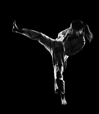 kata: full-length silhouette portrait of beautiful martial arts girl in kimono excercising karate kata kick on black