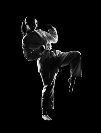full-length silhouette portrait of beautiful martial arts girl in kimono excercising karate kata kick on black photo