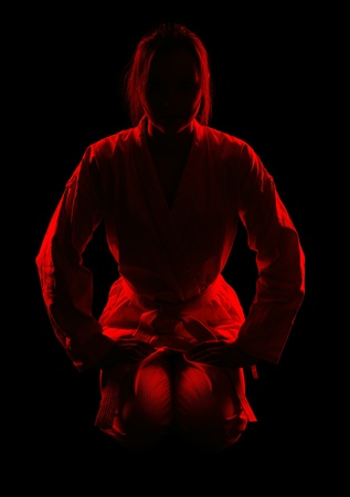 full-length silhouette portrait of beautiful martial arts girl in kimono excercising karate kata on black photo