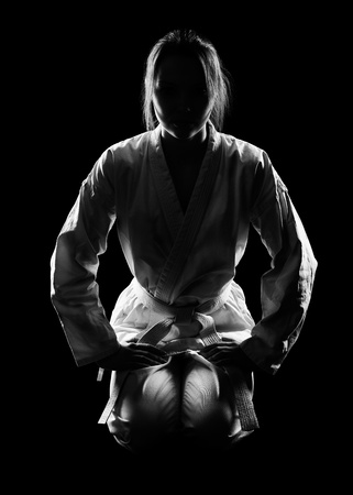 kata: full-length silhouette portrait of beautiful martial arts girl in kimono excercising karate kata on black
