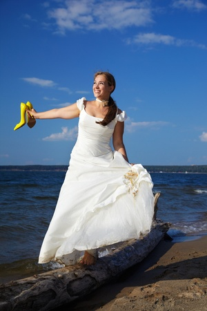 beautiful slavonic bride on sea shore balancing on trunk with yellow court shoes in her hands photo