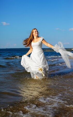 beautiful slavonic bride running in sea waves with bridal in her hands Stock Photo - 9390984